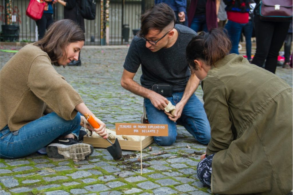 Sofía Dourron, Santiago Villanueva, and Gala Berger, planting Sol Pipkin's work during La Ene's exhibition La Ene in the Open Air, April 2017. Photo by Javier González Tuñón.