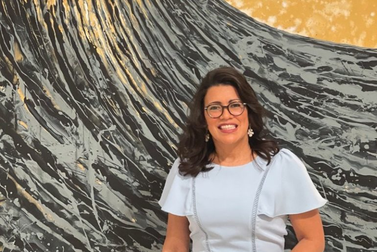 "Curator Paula Gomez Jorgein front of ""The Black Wave and the Angel"" by Eleomar Puente. January 29, 2021"