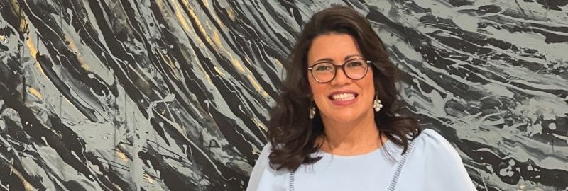 """Curator Paula Gomez Jorgein front of """"The Black Wave and the Angel"""" by Eleomar Puente. January 29, 2021"""